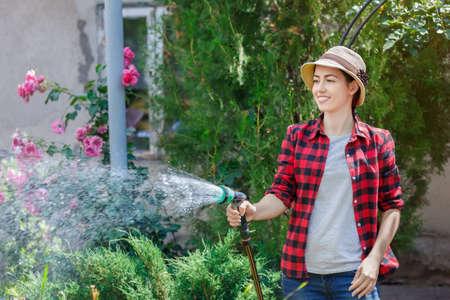Woman gardener watering garden Stockfoto