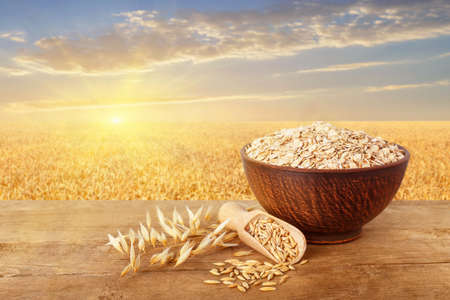 uncooked oatmeal in bowl, scoop with grains, oat ears on table with ripe cereal field on the background. Golden field on sunset. Agriculture and harvest concept. Healthy eating for diet and vegan Stock Photo