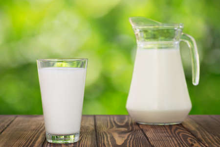 milk in glass and jug on table