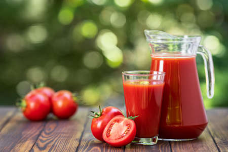 fresh tomato juice in glass and jug with heap of ripe vegetables on wooden table outdoors