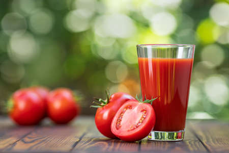 fresh tomato juice in glass with heap of ripe vegetables on wooden table outdoors Zdjęcie Seryjne