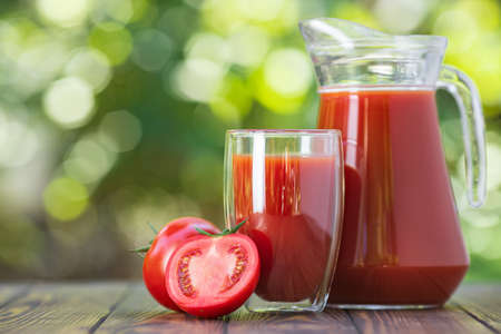 fresh tomato juice in glass and jug with ripe vegetable on wooden table outdoors
