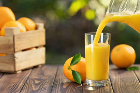 orange juice pouring in glass from jug and ripe fruits in crate on wooden table outdoors. Summer refreshing drink