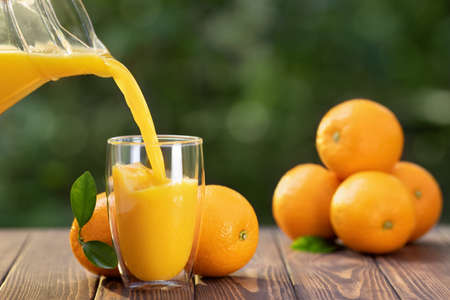 orange juice pouring in glass from jug and ripe fruits on wooden table outdoors. Summer refreshing drink Zdjęcie Seryjne