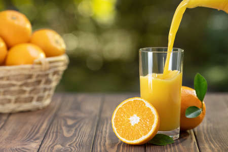 orange juice pouring in glass and ripe fruits in basket on wooden table outdoors. Summer refreshing drink