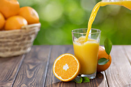 orange juice pouring in glass from jug and ripe fruits in basket on wooden table outdoors. Summer refreshing drink