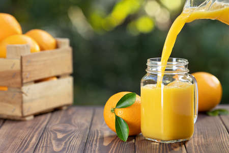 orange juice pouring in glass mason jar from jug and ripe fruits in crate on wooden table outdoors. Summer refreshing drink