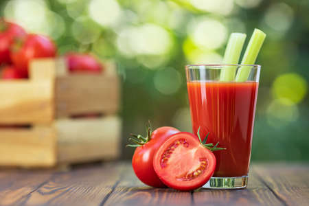 fresh tomato juice in glass with celery sticks and ripe vegetables in crate on wooden table outdoors