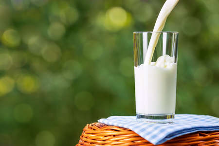 milk pouring into glass on wicker basket with blue checkered napkin outdoors