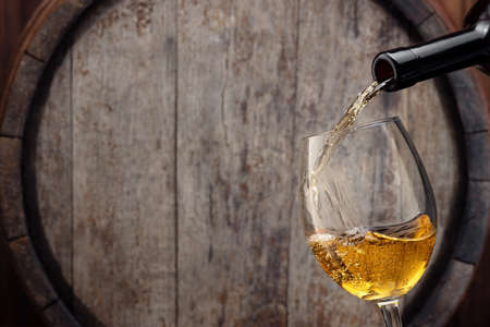 white wine pouring from bottle into glass with old wooden barrel as background