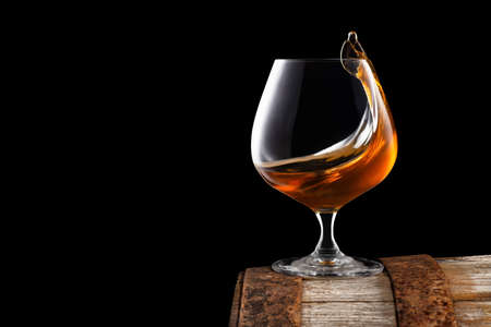 brandy or cognac in snifter glass with wave surface level on old wooden barrel as table isolated on black background