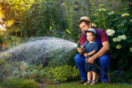 man gardener with grandson watering garden