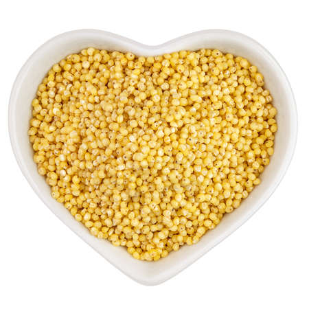 millet groats in heart shaped plate Archivio Fotografico