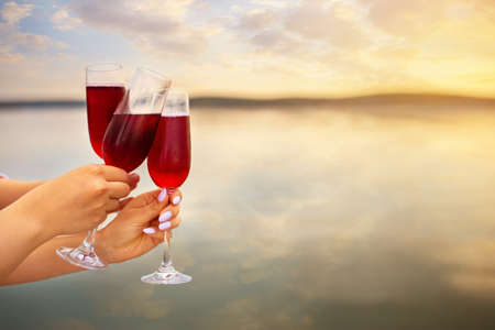 female hands with glasses of red champagne making toast