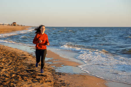 Fitness woman running on the beach Archivio Fotografico