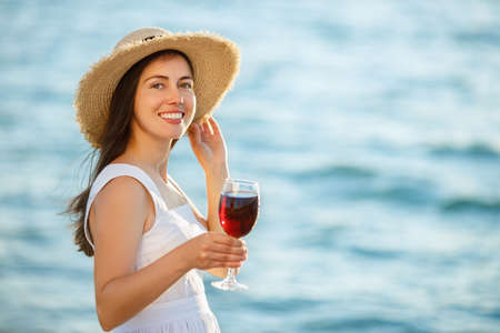 woman holding glass of wine by the sea Archivio Fotografico