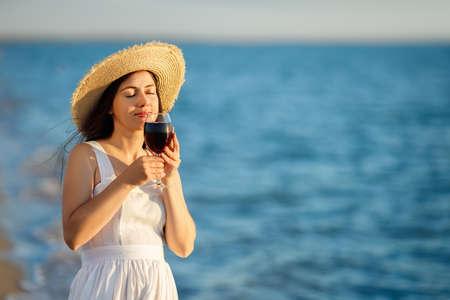 woman holding glass of wine by the sea Zdjęcie Seryjne