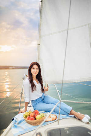 woman with glass of champagne resting on yacht