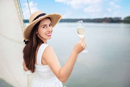 woman with glass of champagne resting on boat Zdjęcie Seryjne