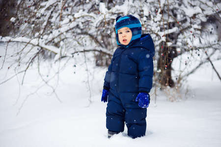 little boy walking on snow in winter outdoors