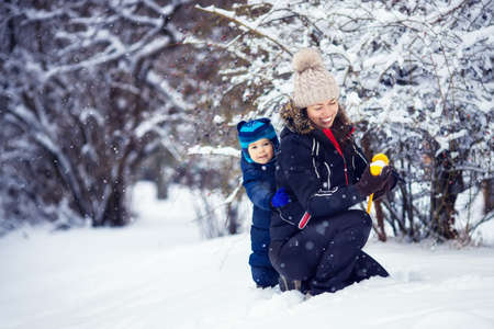 mother and little boy making snowballs