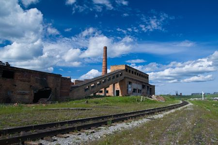 wreckage: Old mine ruins near old rails under the wonderful sky Stock Photo