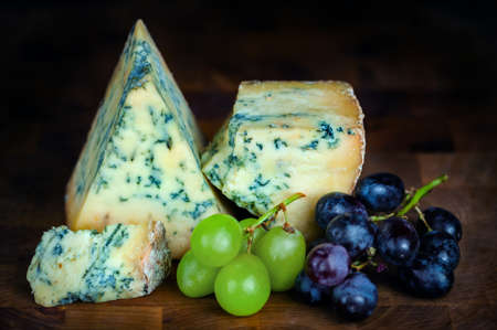 mouldy: Stilton mature blue mouldy cheese - Dark background and grapes Stock Photo