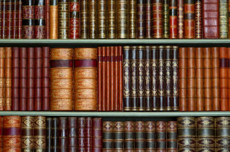 with spines: Old library of vintage hard cover books on shelves