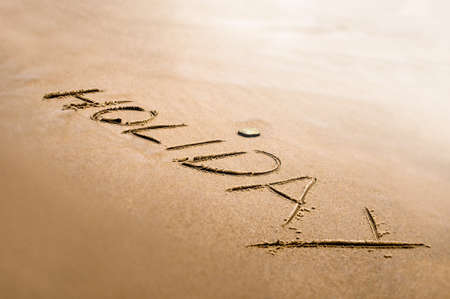 Holiday word written on the sand bright back light effect photo