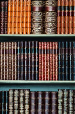 Old library of vintage hard cover books on shelves vertical Banco de Imagens
