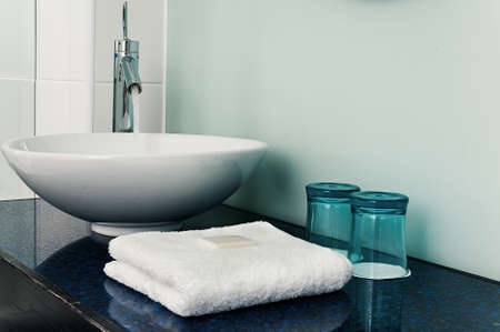 fold: Bathroom sink counter towels water glass blue
