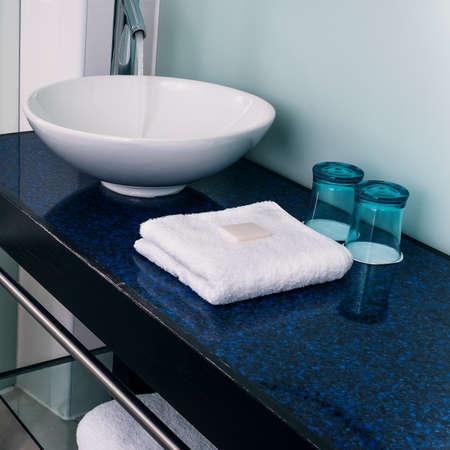 lavabo salle de bain: Salle de bain bleu �vier contre serviettes de verre d'eau Banque d'images