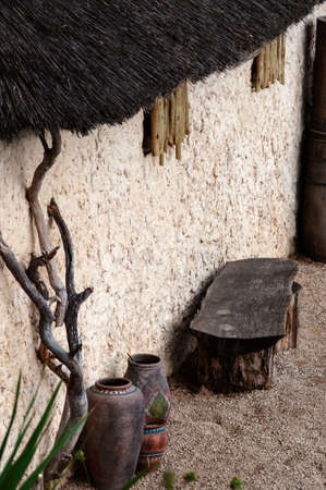 mud house: African village outdoor scene empty bench and pots straw roof