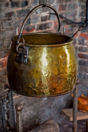 antique background: Single Antique vintage 1590 cauldron hand forged cooking pot hangged by the hearth fireplace old golden Stock Photo