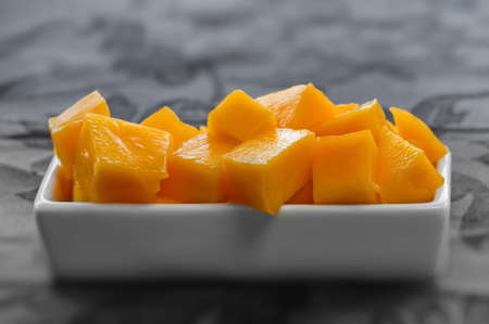 placed: Diced mango cubes placed and served on a white dish closeup Stock Photo