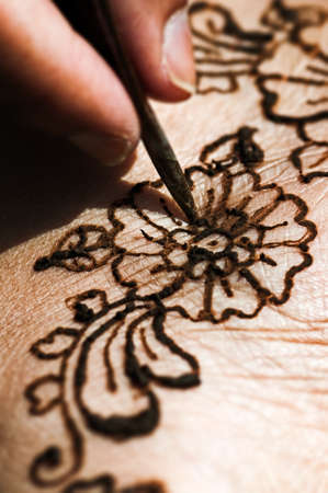 wedding celebration: Henna tattoo drawing with herbal dye on foot floral design macro closeup