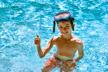 eight years old: Boy kid child eight years old inside swimming pool portrait happy fun bright day diving goggles thumbs up