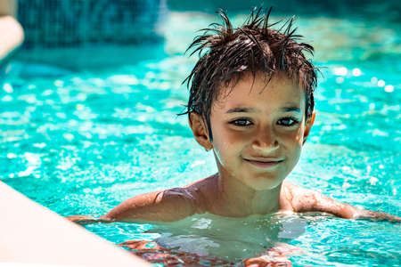 kids playing sports: Boy kid child eight years old inside swimming pool portrait happy fun bright day Stock Photo