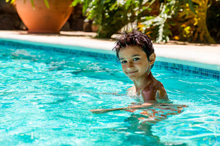 eight years old: Boy kid child eight years old inside swimming pool portrait happy fun bright day Stock Photo