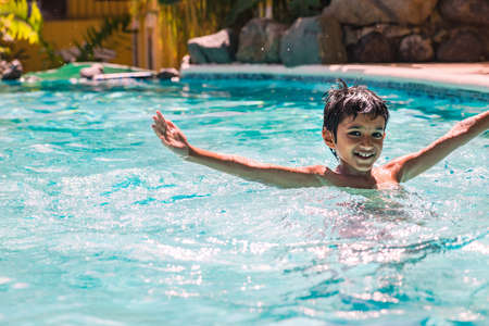 eight years old: Young boy kid child eight years old splashing in swimming pool having fun leisure activity Stock Photo