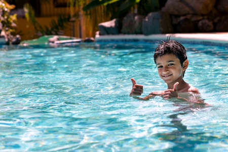 eight years old: Young boy kid child eight years old having fun in swimming pool leisure activity thumbs up Stock Photo