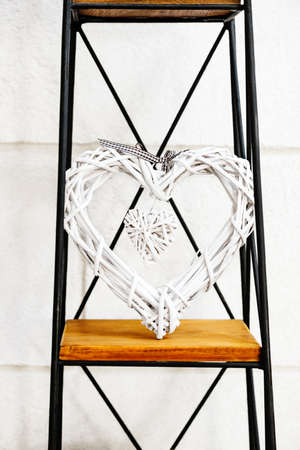 prop: Heart within a heart decorative prop standing on metal and wooden stand against the white wall