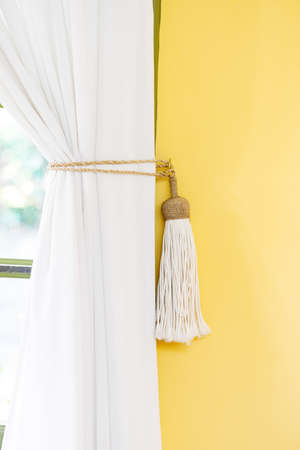 wall decor: White curtain tie-back home decor simple style indoors yellow wall