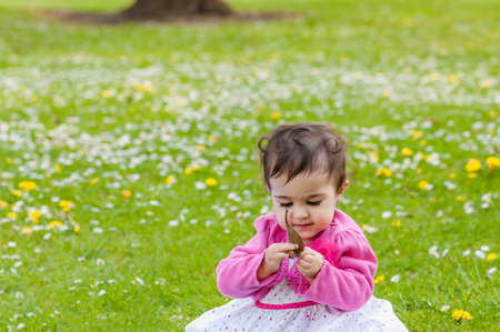 curiously: Cute chubby toddler looking at a leaf curiously exploring nature outdoors in the park Stock Photo