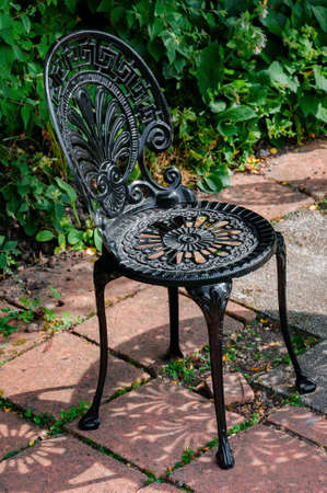 Wrought Cast Iron Chair In The Garden Black Color Stock Photo, Picture And  Royalty Free Image. Image 66618715.
