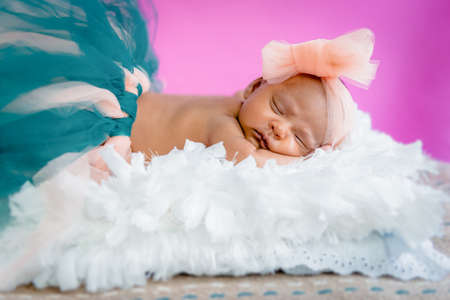 Four weeks baby infant girl studio photo sleeping on fluffy pillow wearing tutu and bow
