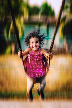 Happy toddler swinging high happy and joyful playing in the park having fun outdoors Banco de Imagens
