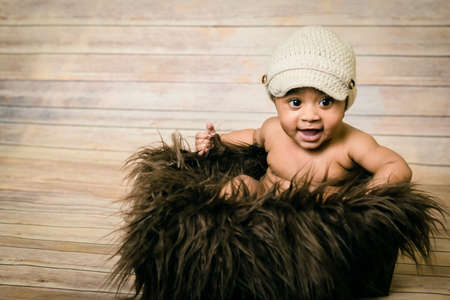 Infant mixed race healthy looking baby boy wearing knitted hat sitting in a fluffy furry basket wooden background modern studio shoot vintage look smiling happy six months old having fun Banco de Imagens