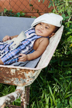 Six month old baby fun concept lying on wheel barrel as if tired from working too hard. Chilling out. Banco de Imagens