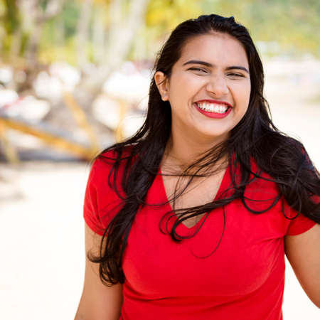 Happy young woman girl with a big smile by the beach enjoying the sunshine. Banco de Imagens